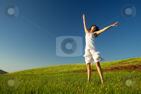 Jumping on the field stock photo, Beautiful young woman jumping on the field by ikostudio