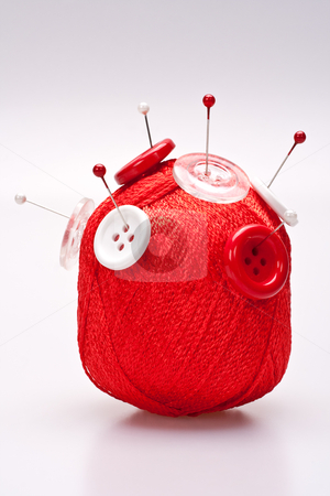 Pins in wool ball with buttons stock photo, red and white pins in red wool ball with buttons by Artem Zamula