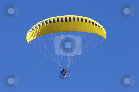 Yellow Parachute with motorized chair stock photo, Yellow Parachute with motorized chair with blue sky background by visceralimage