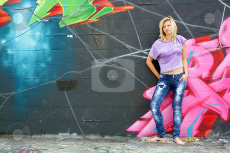 Attractive Blonde with Graffiti (7) stock photo, A lovely young blonde leans against a graffiti-covered wall. by Carl Stewart