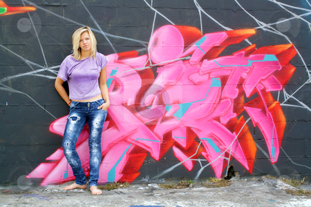 Attractive Blonde with Graffiti (8) stock photo, A lovely young blonde leans against a graffiti-covered wall. by Carl Stewart