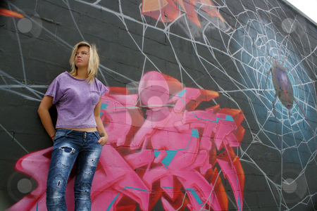 Attractive Blonde with Graffiti (9) stock photo, A lovely young blonde leans against a graffiti-covered wall.  Low angle. by Carl Stewart