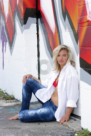 Attractive Blonde with Graffiti (14) stock photo, A lovely young blonde leans against a graffiti-covered wall. by Carl Stewart