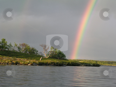 Rainbow stock photo, Beautiful rainbow by the lake by Ingvar Bjork