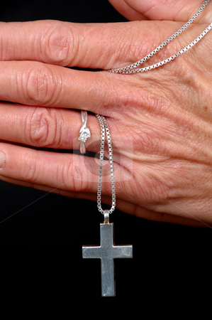 Woman praying stock photo, Woman is praying holding her cross. On black clean background. by Lars Christensen