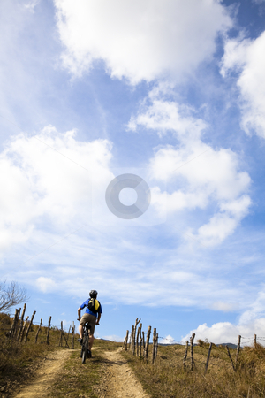 Young man riding mountain bike and watching cloudy sky stock photo, Young man riding mountain bike and watching cloudy sky by tomwang