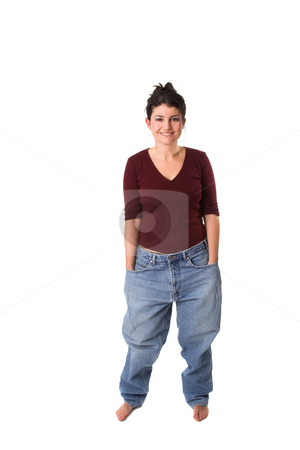 Having lost weight stock photo, Pretty brunette showing off how much weight she has lost by putting on an old pair of jeans by Simone Van den Berg