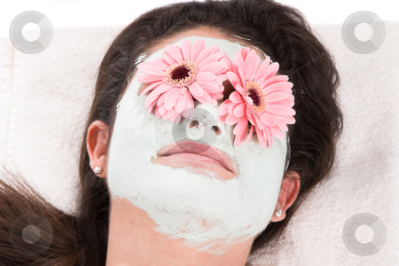Beautymask stock photo, beautiful brunette taking a clay mask with her eyes covered in gerbera flowers by Simone Van den Berg