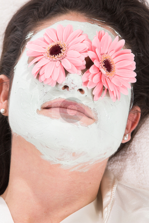 Beauty treatment stock photo, Pretty brunette lying on a towel with a claymask and flowers on her eyes by Simone Van den Berg
