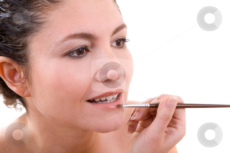 Applying lipgloss stock photo, Beautiful brunette applying lipgloss to her lips with a small brush by Simone Van den Berg