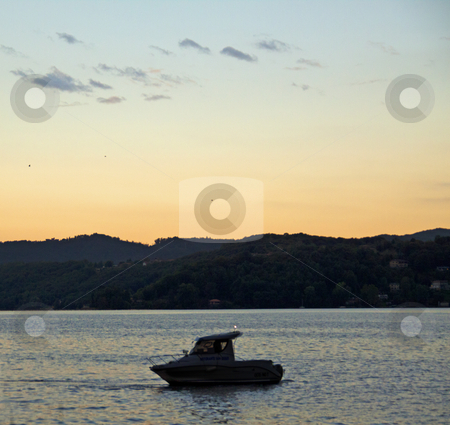 Sunset on the lake stock photo, Silhouette of a boat in a lake, at sunset by Fabio Alcini