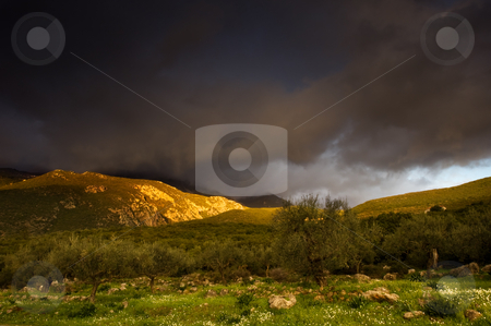Landscape stock photo, Greek landscape right after a storm with emerging rays of sun lighting the tip of the mountain by Andreas Karelias