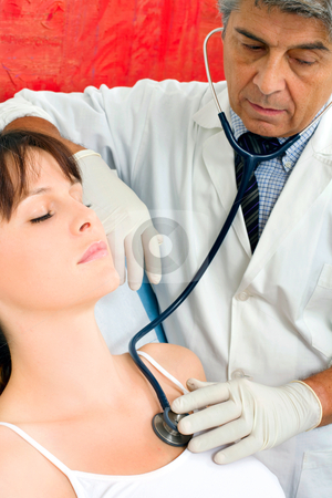 Man doctor visits a young caucasian woman with stethoscope stock photo, man doctor visits a young caucasian woman with stethoscope by ambrophoto