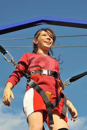 Bungee jumping stock photo, young teenager smiling on the trampoline (bungee jumping). by Bonzami Emmanuelle