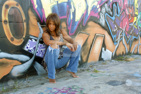 Beautiful Mature Black Woman with Graffiti (4) stock photo, A lovely mature black woman, wearing tattered jeans, squats, leaning against a wall of graffiti art. by Carl Stewart