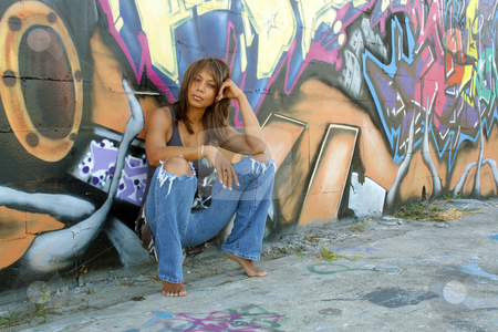 Beautiful Mature Black Woman with Graffiti (5) stock photo, A lovely mature black woman, wearing tattered jeans, squats, leaning against a wall of graffiti art. by Carl Stewart