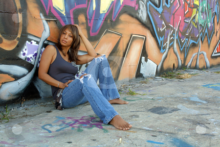 Beautiful Mature Black Woman with Graffiti (6) stock photo, A lovely mature black woman, wearing tattered jeans, sits in front of a wall of graffiti art. by Carl Stewart