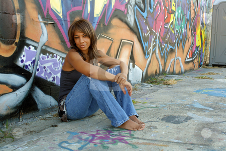 Beautiful Mature Black Woman with Graffiti (7) stock photo, A lovely mature black woman, wearing tattered jeans, sits in front of a wall of graffiti art. by Carl Stewart