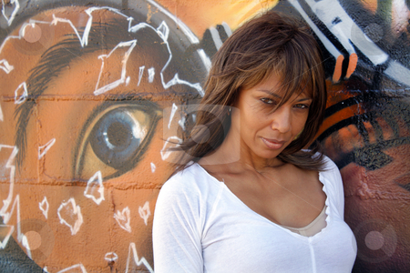 Beautiful Mature Black Woman with Graffiti (9) stock photo, A lovely mature black woman stands in front of a wall of graffiti art. by Carl Stewart