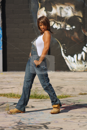 Beautiful Mature Black Woman with Graffiti (10) stock photo, A lovely mature black woman, wearing denim bib overalls with work boots and a white tank top, stands in front of a graffiti skull.  by Carl Stewart