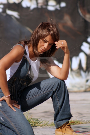 Beautiful Mature Black Woman with Graffiti (11) stock photo, A lovely mature black woman, wearing denim bib overalls with work boots and a white tank top, kneels in front of a graffiti skull.  by Carl Stewart