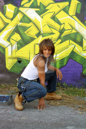 Beautiful Mature Black Woman with Graffiti (12) stock photo, A lovely mature black woman, wearing denim bib overalls with work boots and a white tank top, squats in front of a graffiti-covered block wall. by Carl Stewart