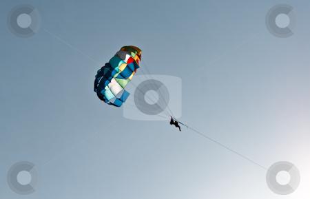Tourists paragliding through blue sky
