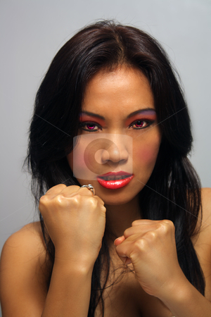 Beautiful Angry Asian Girl with Fists stock photo, A lovely young Indonesial model with long, luscious black hair holds her fists up ready to fight.  Her glowing red eyes match her firey persona. by Carl Stewart