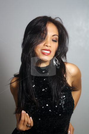 Beautiful Smiling Asian Girl (5) stock photo, A lovely young Indonesian model with long, luscious black hair, and a bright, warm smile, wearing a black sequined dress, with her eyes closed. by Carl Stewart