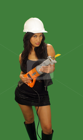 Beautiful Asian Female Construction Worker (1) stock photo, A lovely young and fashionable Indonesian model with long, luscious black hair, holds a reciprocating saw, isolated on a plain green background. by Carl Stewart