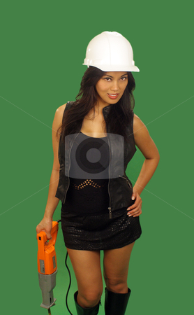 Beautiful Asian Female Construction Worker (3) stock photo, A lovely young and fashionable Indonesian model with long, luscious black hair, holds a reciprocating saw, isolated on a plain green background. by Carl Stewart