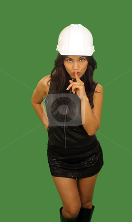 Quiet Asian Female Construction Worker stock photo, A lovely young and fashionable Indonesian model with long, luscious black hair, wearing a white hardhat, isolated on a plain green background, with her index finger over her mouth to indicate quiet. by Carl Stewart