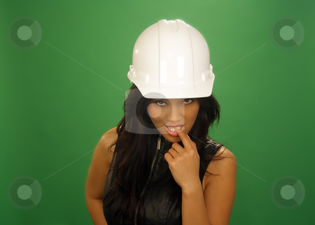Flirtatious Asian Female Construction Worker (2) stock photo, A lovely young and fashionable Indonesian model with long, luscious black hair, wearing a white hardhat, isolated on a plain green background. by Carl Stewart