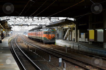 Train at station stock photo, Commuter train arriving at a train station  by Tito Wong