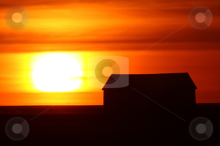 Setting sun backlighting farm buildings stock photo, Setting sun backlighting farm buildings by Mark Duffy