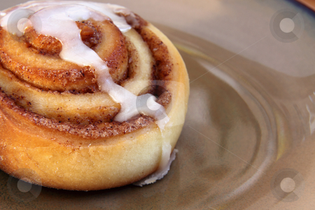 Fresh Cinnamon Bun stock photo, A cinnamon bun sitting on a plate.  by Chris Hill