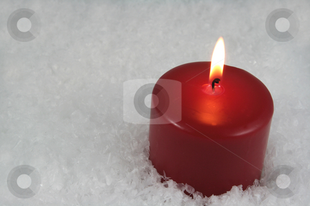 Red Candle on Snow stock photo, A red lit candle sitting in a bed of snow. by Chris Hill
