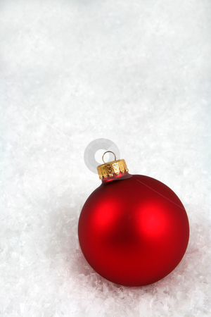 Red Xmas Ball in the Snow stock photo, A red Christmas bauble sitting in a bed of snow.  by Chris Hill