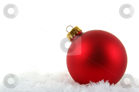 Red Xmas Bauble in the Snow stock photo, A red Christmas bauble sitting in a bed of snow.  by Chris Hill