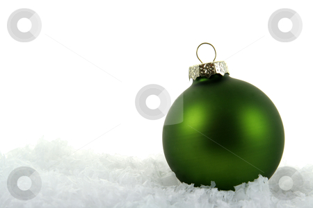 Dark Green Xmas Bauble in the Snow stock photo, A green Christmas bauble sitting in a bed of snow.  by Chris Hill