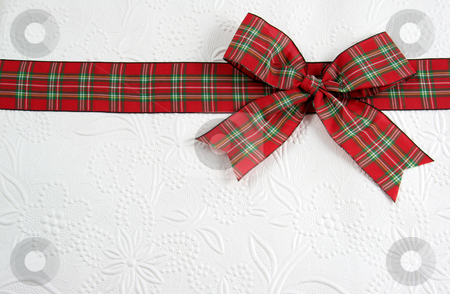 Holiday Plaid Bow stock photo, A plaid christmas bow on decorative white paper.  by Chris Hill