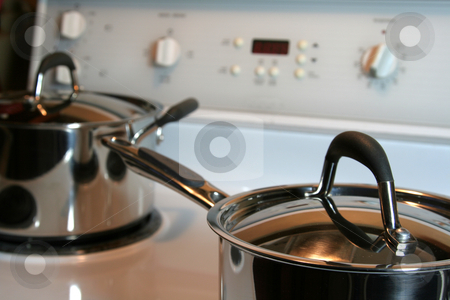 Stainless Steel Pots on the Oven stock photo, Two stainless steel pots sitting on an oven. by Chris Hill