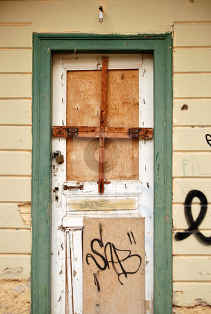 Boarded up door stock photo, Boarded up door and weathered wall surface of an abandoned house. by sirylok
