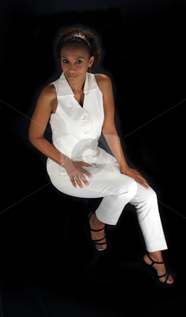 Beautiful Mature Black Woman Sitting (1) stock photo, A lovely mature black woman sits on a black background, allowing you to easily insert something for her to sit on or extract her from the black background to have her sitting on something. by Carl Stewart
