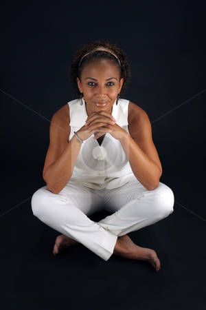 Beautiful Mature Black Woman Sitting (2) stock photo, A lovely mature black woman sits on a black background with her legs crossed, allowing you to easily insert something for her to sit on or extract her from the black background to have her sitting on something. by Carl Stewart