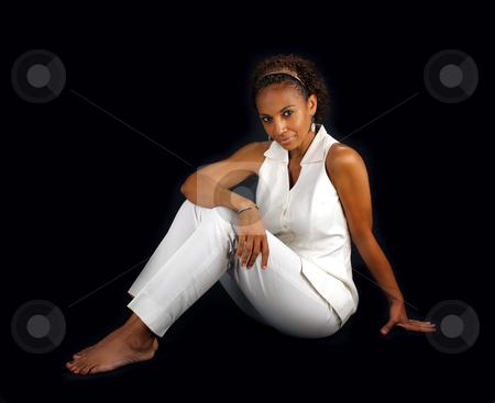 Beautiful Mature Black Woman Sitting (3) stock photo, A lovely mature black woman sits on a black background profile to the camera, allowing you to easily insert something for her to sit on or extract her from the black background to have her sitting on something. by Carl Stewart
