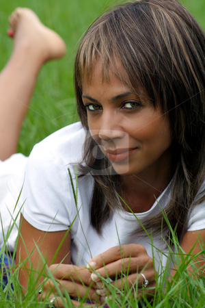 Woman in a Grassy Field (3) stock photo, Close-up of a lovely mature black woman in a grassy field, looking into the camera with a relaxed, pleasant facial expression. by Carl Stewart