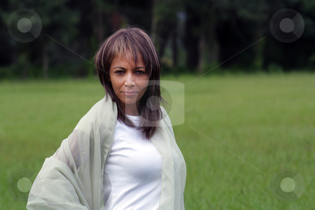 Beautiful Black Woman Outdoors (1) stock photo, A beautiful mature black woman soaks up some atmosphere with a swatch of sheer fabric outdoors, looking directly into the camera. by Carl Stewart