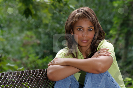 Beautiful Black Woman Outdoors (2) stock photo, A beautiful mature black woman soaks up some atmosphere on a park bench amidst lush tropical vegetation outdoors, looking directly into the camera. by Carl Stewart