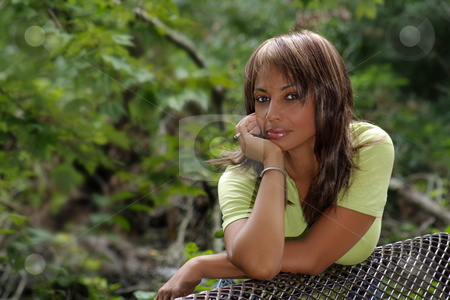 Beautiful Black Woman Outdoors (3) stock photo, A beautiful mature black woman soaks up some atmosphere on a park bench amidst lush tropical vegetation outdoors, looking directly into the camera. by Carl Stewart